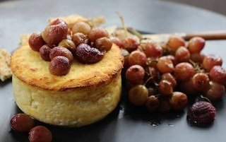 baked ricotta with roasted grapes close up